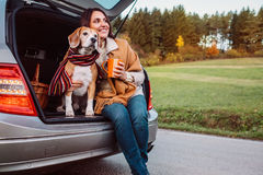 Woman and dog with shawls sits together in car trunk on autumn royalty free stock photography
