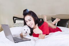 Woman and dog with showing thumb up. Young woman using laptop while hugging a puppy and lying on the bed with showing thumb up in the bedroom Royalty Free Stock Photo
