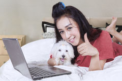 Woman with dog shows thumb up on bed Stock Photos