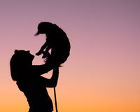 Woman and Dog Silhouette. Woman standing against a sunset and holding her dog up in the air with joy Stock Photo
