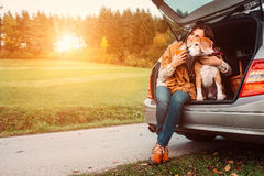 Woman with dog sits in car trunk on autumn road stock photos