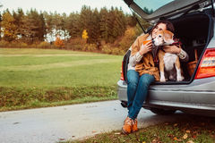 Woman with dog sits in car trunk on autumn road Stock Photo