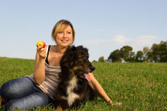 Woman with a dog. Woman sitting with a dog in the grass Royalty Free Stock Images