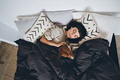 Woman and dog sleep in bed. Beautiful young woman or girl cuddles and hugs her best friend basenji puppy dog, sleep together under blankets in hipster designer Royalty Free Stock Image