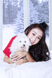 Woman with dog smiling on the bed. Happy young female looking at the camera while hugging a maltese dog and lying on the bed with winter background on the window Stock Photo