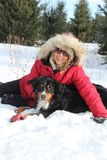 Woman with dog in snow. Woman with red jacket laying in snow with her dog Stock Images