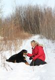 Woman with dog in snow Royalty Free Stock Images