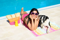 Woman and dog on summer holidays. Happy woman and dog sunbathing together on funny summer at swimming pool. Beautiful girl and her pet wearing sunglasses and stock photo