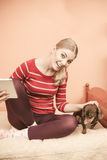 Woman with dog and tablet browsing internet. Stock Photography