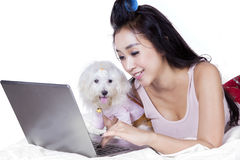 Woman and dog use laptop on bed. Portrait of pretty woman lying on the bed while using notebook computer with a maltese dog Stock Images