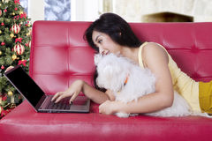 Woman and dog using laptop at home Stock Photography