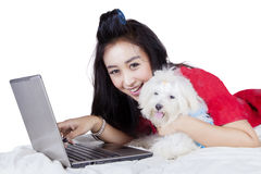 Woman with dog using a laptop on studio. Picture of young Asian woman using a laptop while lying on the bed with Maltese puppy and smiling at the camera Stock Image