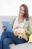 Woman with dog using tablet computer on sofa Royalty Free Stock Images