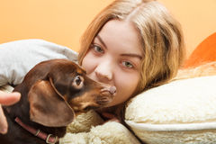 Woman with dog waking up in bed after sleeping. Royalty Free Stock Image