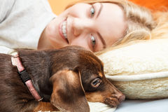 Woman with dog waking up in bed after sleeping. Stock Photos