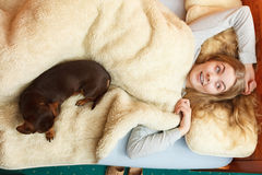 Woman with dog waking up in bed after sleeping. Royalty Free Stock Images