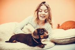 Woman with dog waking up in bed after sleeping. Royalty Free Stock Photography