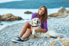 Woman with a dog on a walk on the beach Stock Photos