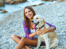Woman with a dog on a walk on the beach Royalty Free Stock Images