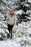 Woman with a dog on walk in a winter wood Stock Photos