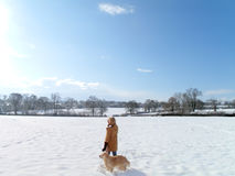 Woman and dog walking in snowy field Royalty Free Stock Photo