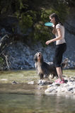 Woman and dog walking in water Royalty Free Stock Photography