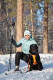 Woman with a dog on walking in winter wood Royalty Free Stock Photo