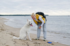 The woman with a dog walks along coast Royalty Free Stock Images