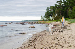 The woman with a dog walks along coast Royalty Free Stock Photo
