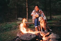 Woman and dog warm near campfire on autumn forest glade royalty free stock images
