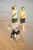 Woman and dog in water running. Two women running and splashing in the water together with their dog Royalty Free Stock Photography