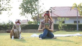 Woman with dog. And holding a tablet stock video