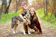 Portrait of Happy Girl and her Pet German Shepherd Dog in Fall Woods. A happy,  thirty year old woman is stopping to hug her German Shepherd dog as they are Stock Images