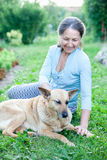 Woman with   dog in   yard. Royalty Free Stock Photography
