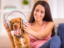 Woman and dog. Young woman and her dog with headphone is listening a music royalty free stock images