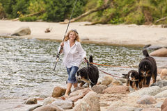 Woman with dogs. Woman with her dogs on sea beach walking Royalty Free Stock Photos