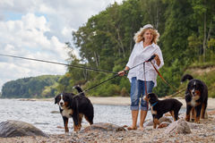 Woman with dogs. Woman with her dogs on sea beach walking Royalty Free Stock Images