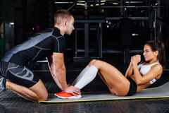 Woman doing abdominal crunches press exercise on the mat with her sports male trainer. Woman doing abdominal crunches press exercise on the mat with her sports Stock Photos