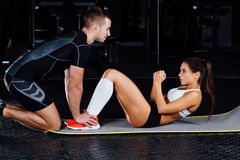 Woman doing abdominal crunches press exercise on the mat with her sports male trainer. Woman doing abdominal crunches press exercise on the mat with her sports Royalty Free Stock Image