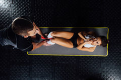 Woman doing abdominal crunches press exercise on the mat with her sports male trainer. Woman doing abdominal crunches press exercise on the mat with her sports Stock Photography