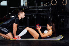 Woman doing abdominal crunches press exercise on the mat with her sports male trainer. royalty free stock image