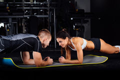 Woman doing abdominal crunches press exercise on the mat with her sports male trainer. Woman doing plank press exercise on the mat with her sports male trainer Royalty Free Stock Image