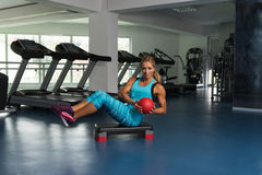 Woman Doing Abdominal Exercise With Ball On Stepper. Mature Woman Athlete Doing Abs Exercise With Ball On Stepper As Part Of Bodybuilding Training Stock Image