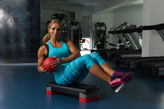 Woman Doing Abdominal Exercise With Ball On Stepper. Mature Woman Athlete Doing Abs Exercise With Ball On Stepper As Part Of Bodybuilding Training Royalty Free Stock Images