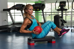 Woman Doing Abdominal Exercise With Ball On Stepper. Mature Woman Athlete Doing Abs Exercise With Ball On Stepper As Part Of Bodybuilding Training Royalty Free Stock Photos