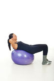 Woman doing abs on pilates ball stock photos