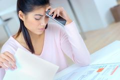 Woman doing accounts making necessary calculations. Worried stock photography