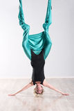 Woman doing aerial yoga upside down on head. Single upside down woman doing aerial yoga with legs wrapped up in large green flexible tarp suspended from ceiling Royalty Free Stock Photo