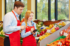 Woman doing apprenticeship in supermarket. Young women doing apprenticeship in supermarket getting help from store manager stock photography