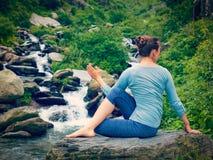 Woman doing Ardha matsyendrasana asana outdoors Stock Photography